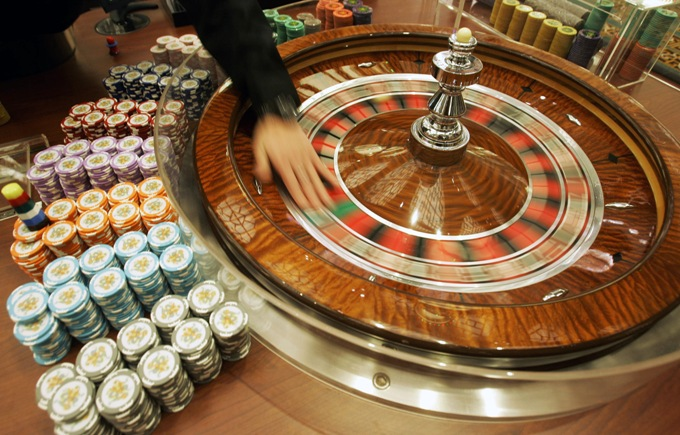"A staff member demonstrates the roulette wheel for the media at the new casino ""Grand Lisboa Casino"" in Macau, Sunday, Feb. 11, 2007. Billionaire gambling king Stanley Ho celebrated the long-awaited opening Sunday of his Grand Lisboa casino _ a gleaming gold complex that is Ho's biggest response to American rivals who have stormed into Macau and seized big chunks of the gaming market.  (AP Photo/Kin Cheung) ORG XMIT: XKC132"